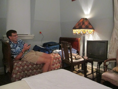 Mark relaxes on the spare bed, near the antique television.
