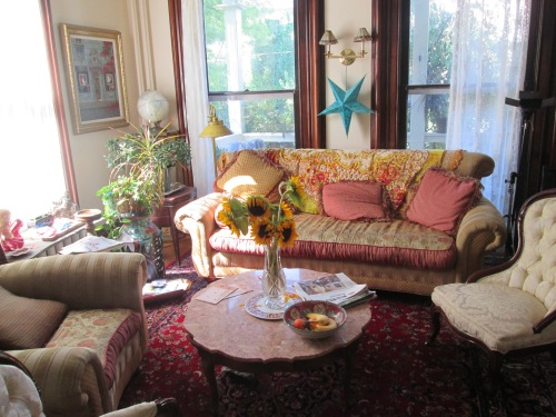 The living room was shabby, though filled with fresh flowers and fruit.